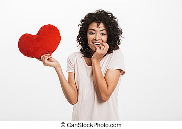 Portrait of lovely woman 20s with brown hair holding red paper heart symbol in valentine day, isolated over white background