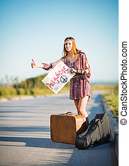 Portrait of lovely young hippie girl hitchhiking on a road