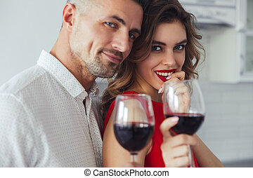 Portrait of lovers drinking wine and looking camera at home