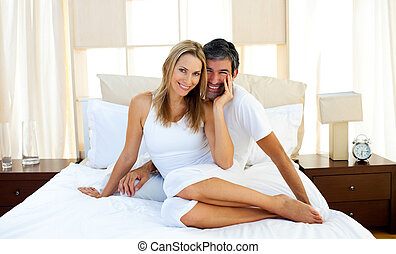 Portrait of lovers sitting on bed