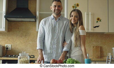 Portrait of loving couple smiling ang looking into camera in the kitchen at home