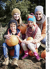 Portrait of loving family with pumpkins