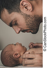 Portrait of loving father with baby at home. Sepia Toned