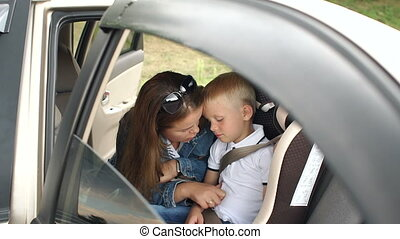 Portrait of loving mother with her son in the car, the boy is wearing a seat belt