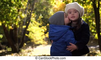 Portrait of loving toddler siblings in autumn park