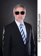Portrait Of Male Body Guard Over Black Background
