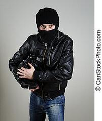 Portrait of male burglar with a handbag.