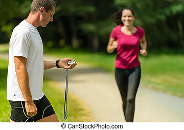 Portrait of male coach timing runner outdoors - Portrait of ...