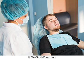 Portrait of male.. Dental care Concept. Dental inspection is being given to beautiful man surrounded by dentist