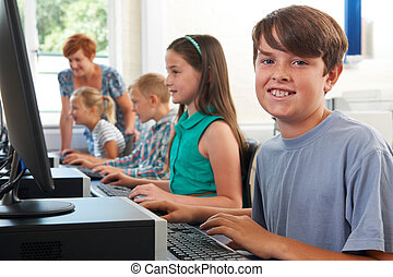 Portrait Of Male Elementary Pupil In Computer Class With Teacher