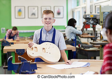 Portrait Of Male High School Student Building Guitar In Woodwork Lesson