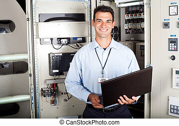 portrait of male industrial engineer in front of machinery