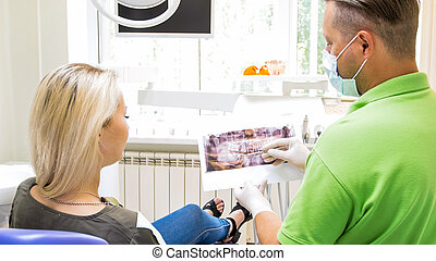 Portrait of male orthodontist talking to his patient and showing x-ray image