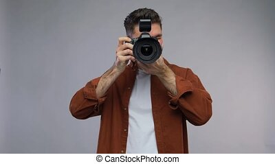 photography, profession and people and concept - video portrait of happy smiling man or photographer with digital camera over grey background