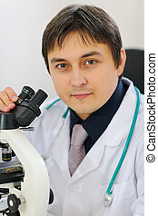 Portrait of male researcher working with microscope