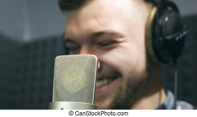 Portrait of male singer in headphones smiling at sound studio during working process. Young man emotionally recording new song. Working of creative musician. Show business concept. Slow motion