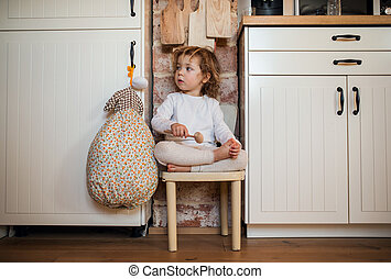 Portrait of mall girl sitting indoors in kitchen at home.