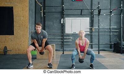 Portrait of man and woman exercising with kettlebells in ...