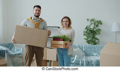 Portrait of man and woman holding boxes during relocation smiling looking at camera standing indoors in new house together. People and housing concept.