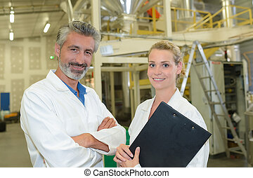 Portrait of man and woman in factory