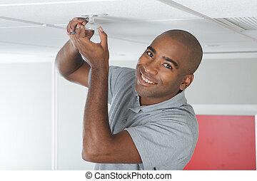 Portrait of man changing lightbulb