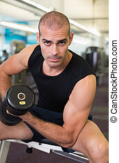 Portrait of man exercising with dumbbell in gym