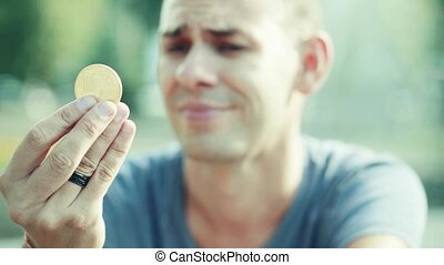 Portrait of man holding bitcoin in his hand. He looking at...