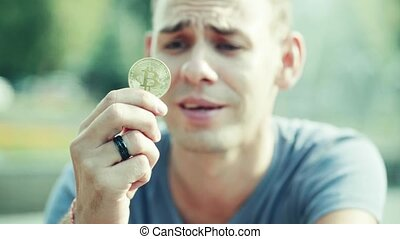 Portrait of man holding bitcoin in his hand.