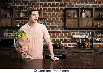 man holding paper bag with food - portrait of man holding...