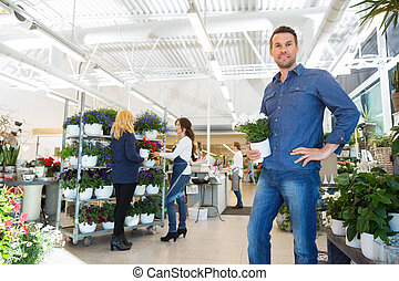 Portrait Of Man Holding Pot Plant In Flower Shop