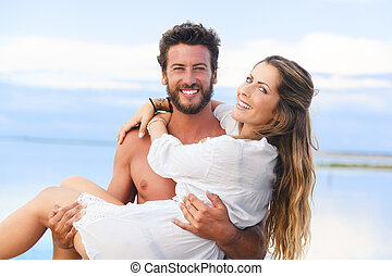 man holding woman in his arms under a blue sky on seaside backgr