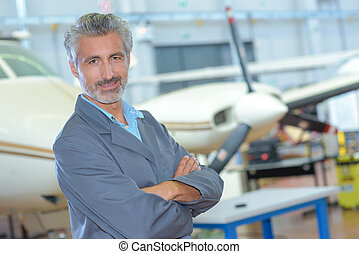 Portrait of man in aircraft hangar