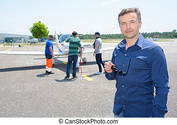 Portrait of man in airport, technicians checking his plane