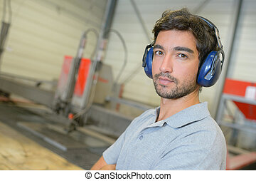 Portrait of man in factory, wearing earmuffs