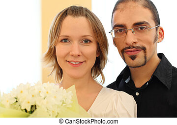portrait of man in glasses and beauty blond girl with flowers bouquet, looking at camera