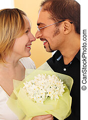 portrait of man in glasses and beauty blond girl with flowers bouquet, looking to each other