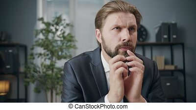 Portrait of mature man dressed in business suit sitting at modern office and thinking about new project. Concept of business career and ideas.