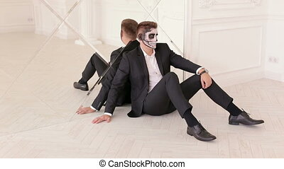 Portrait of man in suit with Halloween skull make-up. Halloween.