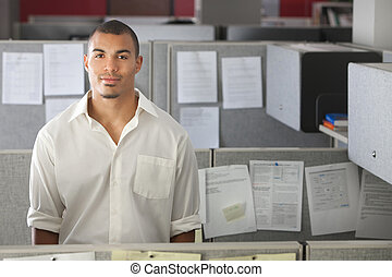 Portrait of handsome man standing in office cubicle
