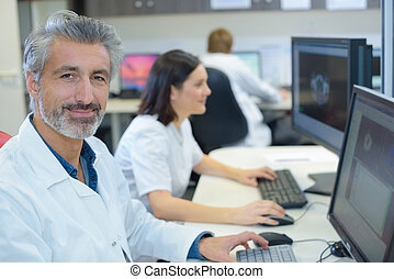 Portrait of man in white coat using computer