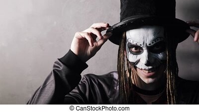 Guy with scary makeup in black hat and dreads hairs. Portrait of man in witcher costume looking at camera and smiling viciously on grey background. Celebrating Halloween holiday concept. Ghost freak.
