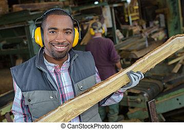 Portrait of man in woodyard holding stake of wood