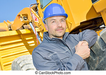 Portrait of man next to heavy plant machinery