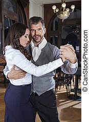 Portrait Of Man Performing Tango With Woman In Restaurant