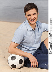 Portrait of man posing on beach with ball. Young man sitting with ball on beach.