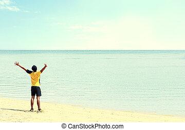man raised arm on the beach