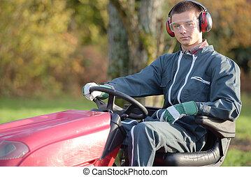 Portrait of man sat on mower