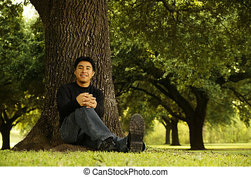 Portrait Of Man Sitting By Tree