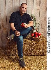 man sitting on hay bale holding an apple