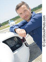 Portrait of man stood next to plane